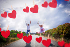 Composite image of excited couple jumping on the road Royalty Free Stock Photography