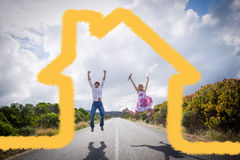 Composite image of excited couple jumping on the road Stock Image