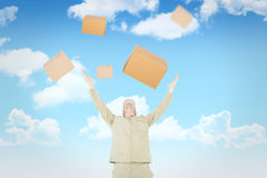 Composite image of excited delivery man with arms raised looking up. Excited delivery man with arms raised looking up against blue sky Stock Photo