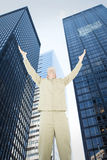 Composite image of excited delivery man with arms raised looking up. Excited delivery man with arms raised looking up against low angle view of skyscrapers Royalty Free Stock Photo