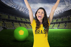 Composite image of excited football fan in brasil tshirt Stock Photos