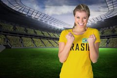 Composite image of excited football fan in brasil tshirt