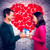 Composite image of excited girlfriend taking gift from boyfriend Royalty Free Stock Photo