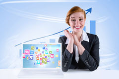 Composite image of excited redhead businesswoman sitting at desk Royalty Free Stock Photos