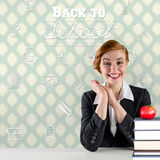 Composite image of excited redhead teacher sitting at desk Royalty Free Stock Photos