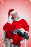 Composite image of excited santa claus talking on mobile phone. Excited Santa Claus talking on mobile phone against white light dots on red royalty free stock photo