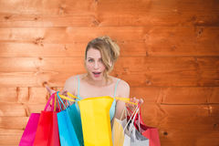 Composite image of excited woman looking at camera with many shopping bags. Excited woman looking at camera with many shopping bags against overhead of wooden Stock Image