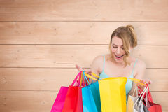 Composite image of excited woman looking at many shopping bags. Excited woman looking at many shopping bags against overhead of wooden planks Royalty Free Stock Photo