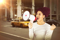 Composite image of excited woman shouting with megaphone. Excited woman shouting with megaphone  against picture of a city Stock Photos