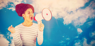 Composite image of excited woman shouting with megaphone. Excited woman shouting with megaphone  against view of beautiful sky and clouds Stock Photos