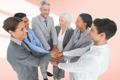 Composite image of executives holding hands together in office. Executives holding hands together in office against red vignette stock photos
