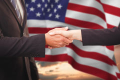 Composite image of executives shaking hands. Executives shaking hands against blue and orange sky with clouds stock image