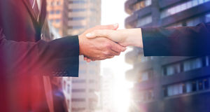 Composite image of executives shaking hands. Executives shaking hands against view of the city buildings royalty free stock photography