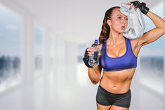 Composite image of exhausted woman wiping sweat while holding water bottle Stock Image