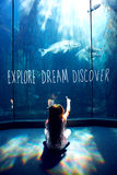 Composite image of explore, dream, discover. Explore, dream, discover against little girl looking at fish tank Stock Image