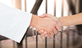Composite image of extreme closeup of a doctor and patient shaking hands Stock Photos