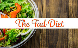Composite image of the fad diet. The fad diet against healthy bowl of salad on table royalty free stock image