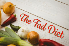 Composite image of the fad diet. The fad diet against various vegetables on wooden table stock photography