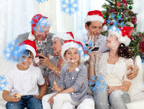 Composite image of family celebrating christmas with wine and sweets at home Stock Photo