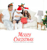 Composite image of family on christmas day looking at their presents at home Stock Photo
