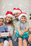 Composite image of family in christmas hat holding presents on sofa Stock Images