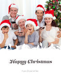 Composite image of family drinking wine and eating sweets in christmas Royalty Free Stock Photos