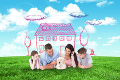 Composite image of family looking at puppy while lying. Family looking at puppy while lying against blue sky over green field Stock Image