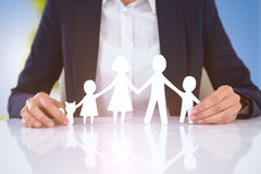 Composite image of family in paper with a man in the background royalty free stock photography