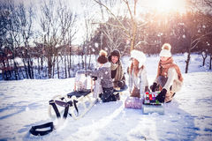 Composite image of family playing with sled on snowy field Stock Photography