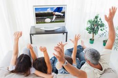 Composite image of family raising their arms in front of television Stock Image