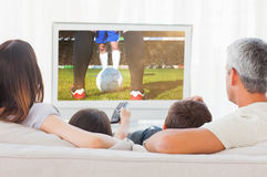 Composite image of family sitting on sofa watching television together Royalty Free Stock Photos
