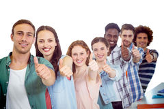 Composite image of fashion students showing thumbs up. Fashion students showing thumbs up against white background with vignette Royalty Free Stock Photography