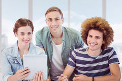 Composite image of fashion students using tablet Royalty Free Stock Photo