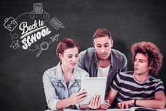 Composite image of fashion students using tablet. Fashion students using tablet  against green chalkboard Stock Image