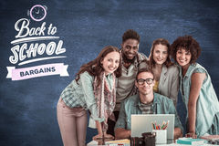 Composite image of fashion students working as a team. Fashion students working as a team  against blue chalkboard Stock Photography