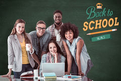 Composite image of fashion students working as a team. Fashion students working as a team  against green chalkboard Royalty Free Stock Photos
