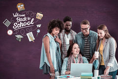 Composite image of fashion students working as a team. Fashion students working as a team  against green chalkboard Royalty Free Stock Images