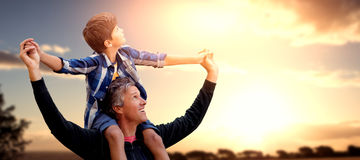 Composite image of father carrying his son on his shoulders. Father carrying his son on his shoulders against landscape of the countryside Royalty Free Stock Images