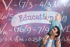 Composite image of father carrying son on shoulders. Father carrying son on shoulders against education against blue chalkboard Stock Images