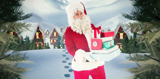 Composite image of father christmas holding many gifts Stock Image