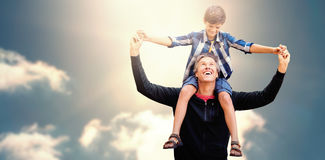 Composite image of father giving his son piggyback ride. Father giving his son piggyback ride against cloudy sky with sunshine Royalty Free Stock Images