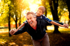 Composite image of father giving his son piggyback ride. Father giving his son piggyback ride against defocused image of trees growing at park Royalty Free Stock Images