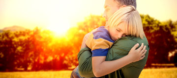 Composite image of father holding his sleeping son. Father holding his sleeping son  against sun rise over trees Royalty Free Stock Photography
