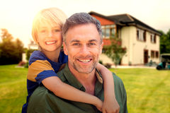Composite image of father holding his son on his back. Father holding his son on his back against view of beautiful house from golf course royalty free stock photo