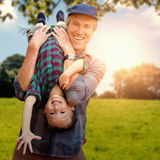 Composite image of father holding his son upside down stock photo