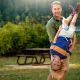 Composite image of father holding son upside-down Stock Photography
