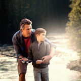 Composite image of father teaching his son fishing. Father teaching his son fishing  against river flowing through forest Stock Photography