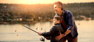 Composite image of father teaching his son fishing. Father teaching his son fishing against view of sea and landscape stock images