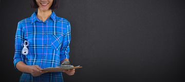 Composite image of female architect holding clipboard and blueprint against grey background. Female architect holding clipboard and blueprint against grey royalty free stock photos