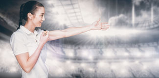 Composite image of female athlete blowing a whistle and pointing Stock Image